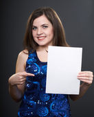 Attractive young woman in a blue dress. Woman holds a poster in — Stock Photo