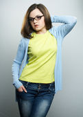 Attractive young woman in a yellow shirt, jeans and glasses. Wom — Stock Photo