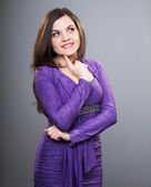 Happy young woman in a lilac dress. Woman holds her finger on he — Stock Photo