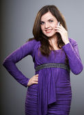 Happy young woman in a lilac dress. Woman talking on mobile phon — Stock Photo