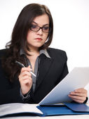 Attractive young woman in a black jacket and glasses sitting at — Stock Photo