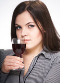 Attractive young woman in a gray shirt. Woman holds a glass of w — Stock Photo