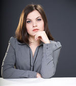 Attractive young woman in a gray blouse sitting at the table. — Stock Photo