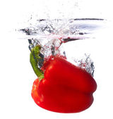 Fresh red paprika falling into the water with a splash of water. — Stock Photo