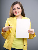 Attractive young woman in a yellow jacket. Woman holds a poster — Stock Photo