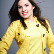 Happy young woman in yellow jacket. Hair in motion. — Foto Stock