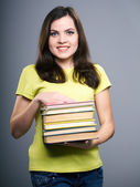 Attractive young woman in a yellow shirt and jeans. Woman holds — Stock Photo