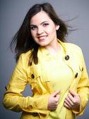 Mulher jovem feliz na jaqueta amarela. cabelos em movimento. — Foto Stock