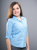 Attractive young woman in a blue shirt and a gray skirt. — Stock Photo