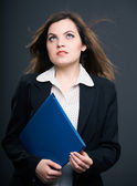 Attractive young woman in a black jacket. Woman holds a blue fol — Stock Photo