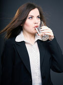 Attractive young woman in a black jacket. Woman drinking mineral — Stock Photo