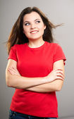 Attractive young woman in a red shirt. Woman standing with folde — Stock Photo