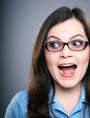 Surprised young woman in a blue blouse and glasses. Looking to t — Stock Photo