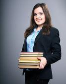 Mulher jovem e atraente com um casaco preto. mulher detém um livros. — Fotografia Stock