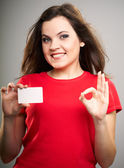 Attractive young woman in a red shirt. Woman holds a poster and — Stock Photo