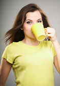Attractive young woman in a yellow shirt. Woman drinking from a — Stock Photo
