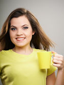 Attractive young woman in a yellow shirt. Woman holds a yellow c — Stock Photo