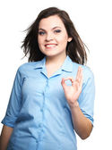 Attractive young woman in a blue shirt. Woman shows a sign okay. — Foto Stock