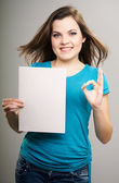 Attractive young woman in a blue shirt. Woman holds a poster and — ストック写真