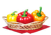 Fresh colorful peppers in a basket. Basket standing on a red nap — Stock Photo