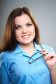 Attractive young woman in a blue blouse. Woman holding glasses. — Stock Photo