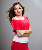 Attractive young woman in a red shirt. Hair in motion — Stockfoto
