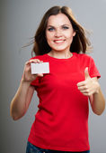 Attractive young woman in a red shirt. Holds a poster and showin — Stock Photo