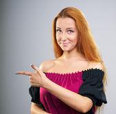 有魅力的年轻女人在一件衣服。显示了她的手指向右 — 图库照片