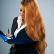 Attractive young woman in a black jacket. Holds a blue folder an — Stock Photo