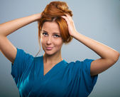 Attractive young woman with red hair in a blue dress. — Stock Photo