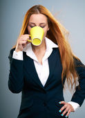 Attractive young woman in a black jacket. Drinking from yellow c — Stock Photo