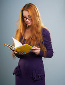 Attractive young woman in a lilac dress and glasses. Woman readi — Stock Photo