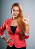 Attractive young woman in a red jacket. Shows sign okay. — Stock Photo