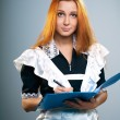 Attractive young woman in a school uniform. Holds a blue folder. — Stock Photo