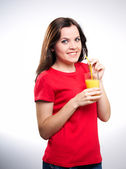 Attractive young woman in a red shirt. Holding a glass of juice. — Stock Photo