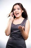 Verrast jonge vrouw in een grijze zakelijke jurk. vrouw praten over — Stockfoto