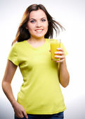 Young beautiful girl in a yellow shirt holding a orange juice — Stock Photo