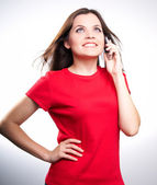 Attractive smiling young woman in a red shirt talking on a mobil — Stock Photo
