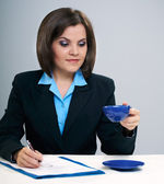 Young attractive businesswoman sitting at a table. Holds a blue — Stockfoto