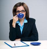 Unga attraktiva affärskvinna i glas. dricka från en blå — Stockfoto