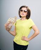 Attraktive junge frau in ein gelbes hemd und sonnenbrille. hält ein — Stockfoto