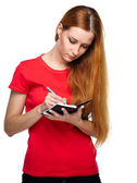 Attractive young woman in a red shirt. Writes in a notebook. — Stock Photo
