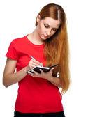 Attraktive junge frau in ein rotes hemd. schreibt in einem notizbuch. — Stockfoto
