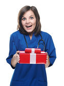 Surprised young nurse holding a gift box. Isolated on white back — Stock Photo