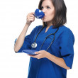 Attractive young nurse drinking from a blue cup.  — Zdjęcie stockowe
