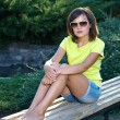 Attractive young woman in a yellow shirt and glasses. Woman sitt — Stock Photo #31471561