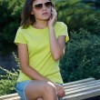 Attractive young woman in a yellow shirt. Woman sitting on a ben — Stock Photo