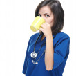 Attractive young nurse with a stethoscope drinking from a yellow — Stock Photo