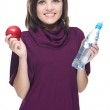 Attractive young woman in a red dress. Holding a bottle of miner — Stock Photo #31475631