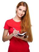 Joven atractiva con una camisa roja. escribe algo en un no — Foto de Stock